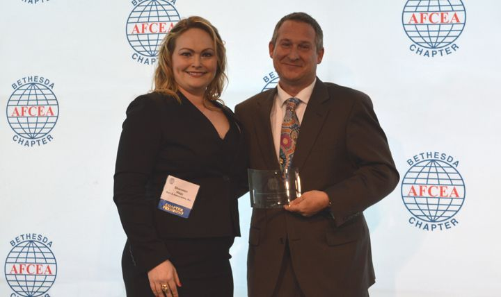 Shannon Hagy, president of the Bethesda, Maryland, chapter of the Armed Forces Communications and Electronics Association, presents Mark Goodge, the Military Health System's chief technology officer, with the InnovateIT Outstanding Achievement Award-DoD. (Courtesy photo)